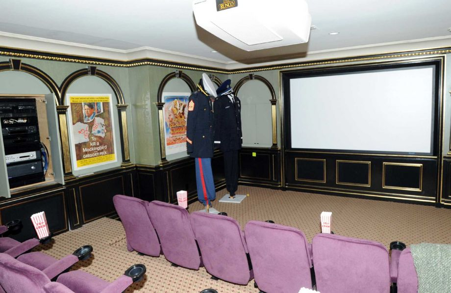 This is the home theater room of the mansion with a large screen at the far end across from rows of pink upholstered theater chairs. Image courtesy of Toptenrealestatedeals.com.