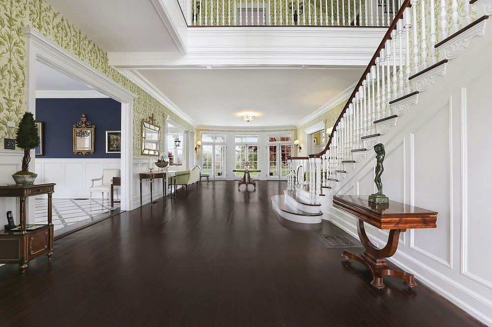 Upon entry of the house, you are welcomed by this foyer that has a dark hardwood flooring to contrast the white walls adorned with wallpaper. Image courtesy of Toptenrealestatedeals.com.