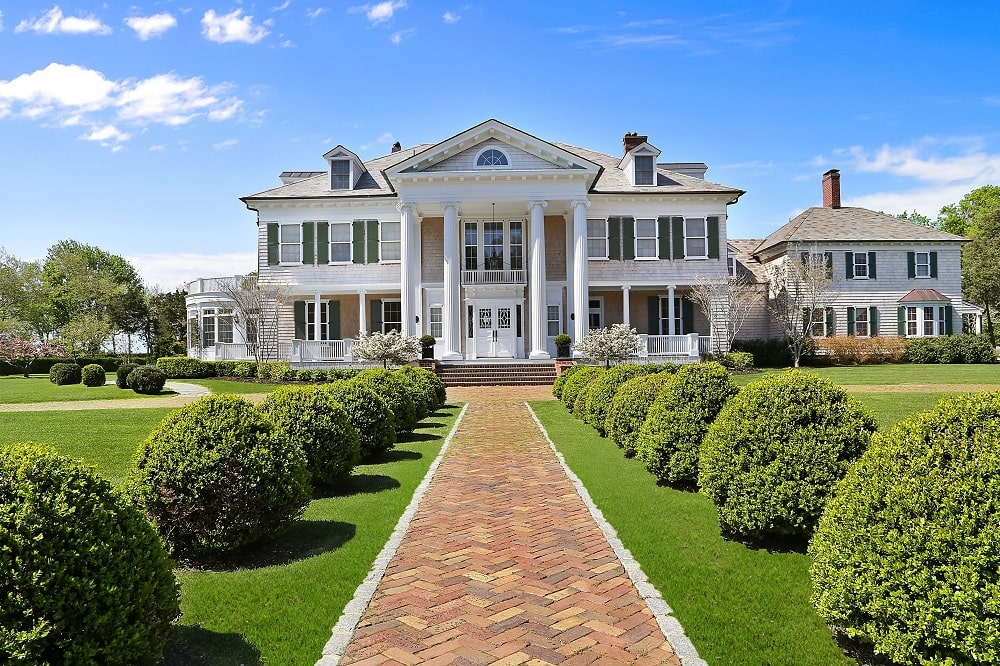 This is a front view of the mansion showcasing its bright exteriors that has balconies, pillars and large windows. These are then complemented by the large front lawn with shrubs and a bricked walkway. Image courtesy of Toptenrealestatedeals.com.