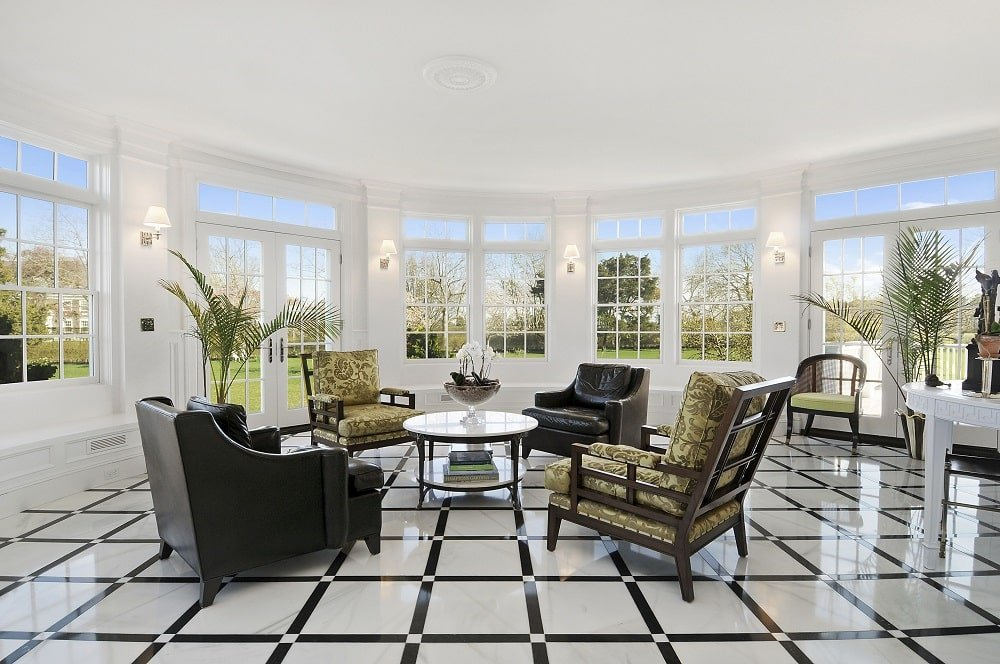 This is the living room and sitting room with a patterned flooring, armchairs and a round coffee table enlightened by the surrounding glass windows. Image courtesy of Toptenrealestatedeals.com.