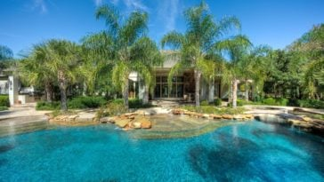 This is a view of the main house of the estate from the vantage of the backyard pool. Here you can see the glass walls and exteriors of the house complemented by tall tropical trees. Image courtesy of Toptenrealestatedeals.com.