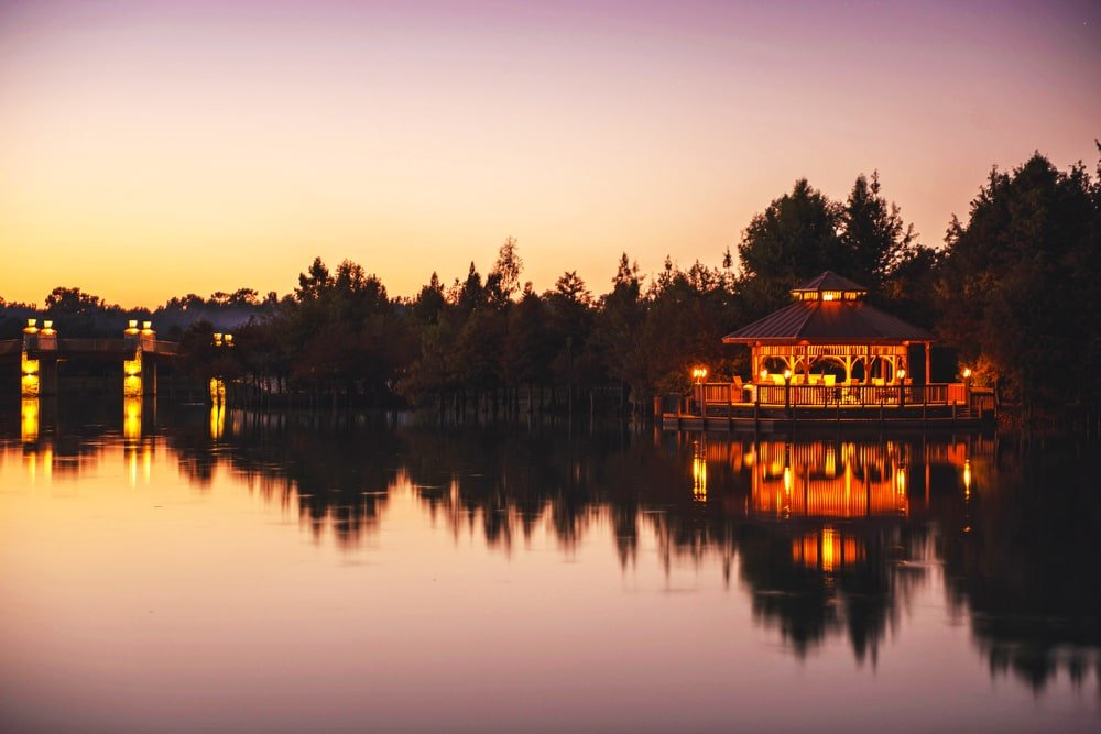 This is a nighttime view of the gazebo by the lake that has warm lighting that reflects on the lake. Image courtesy of Toptenrealestatedeals.com.