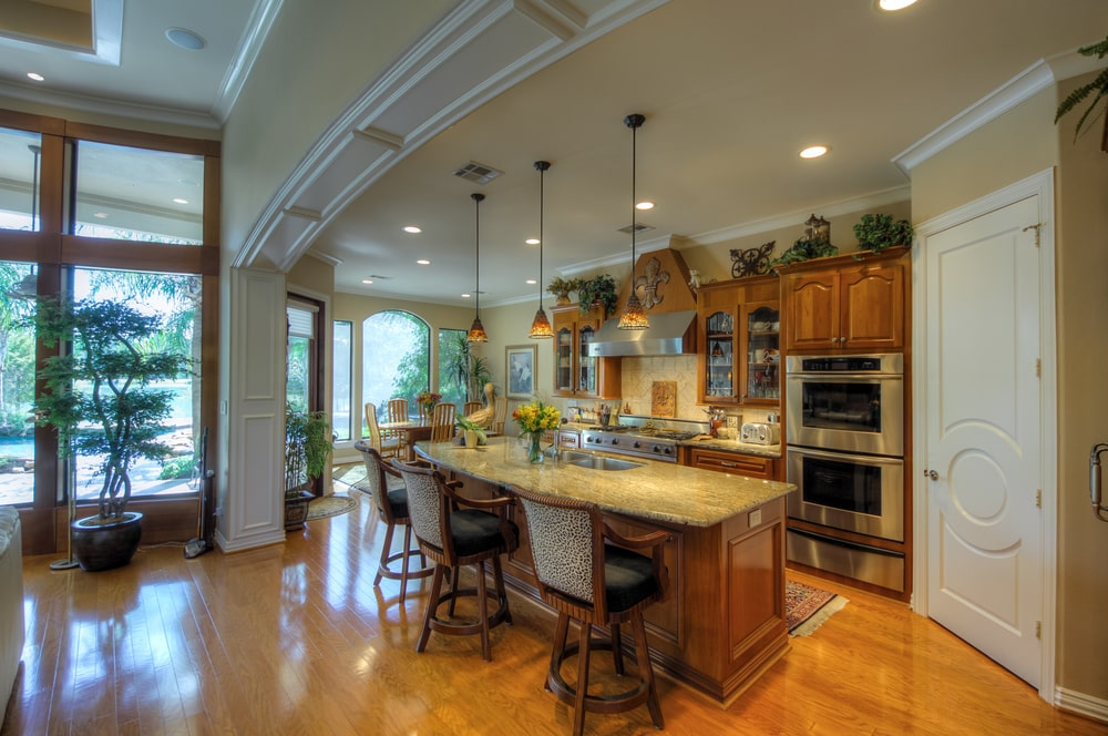 This is the kitchen of the main house with a large kitchen island with brown wooden cabinetry that makes the stainless steel appliances stand out. Image courtesy of Toptenrealestatedeals.com.