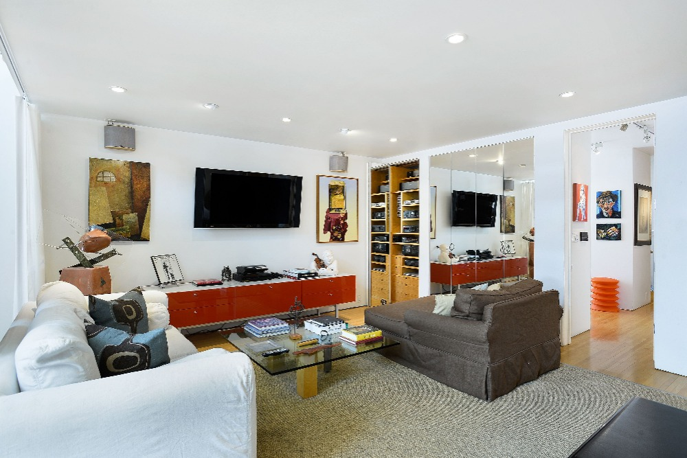 Living space featuring a set of comfy seats and a widescreen TV on the wall. Image courtesy of Toptenrealestatedeals.com.