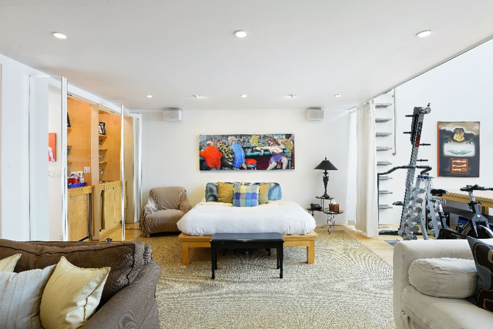 Focused look at the bedroom's cozy bed set with an armchair on the side. Image courtesy of Toptenrealestatedeals.com.