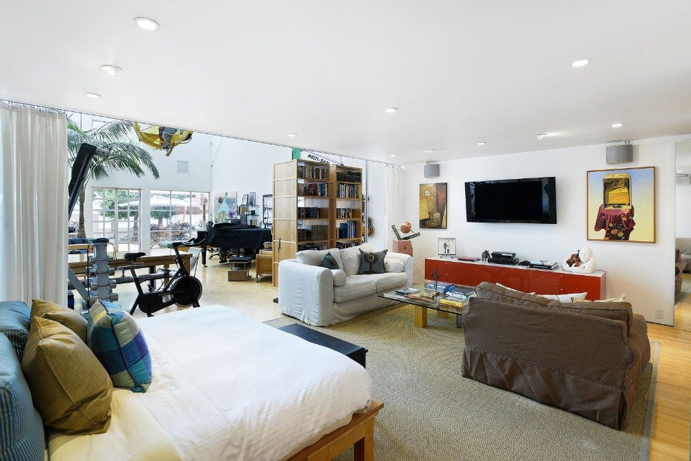 Bedroom featuring a personal living space with a widescreen TV on the wall. Image courtesy of Toptenrealestatedeals.com.