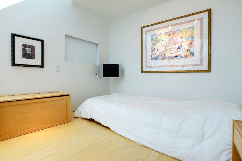 Bedroom with a single bed set along with a small monitor on the wall. Image courtesy of Toptenrealestatedeals.com.