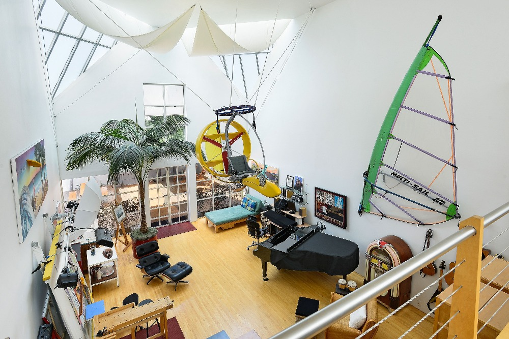 A view of the room from the second floor featuring the black piano on the side and the home's custom ceiling. Image courtesy of Toptenrealestatedeals.com.