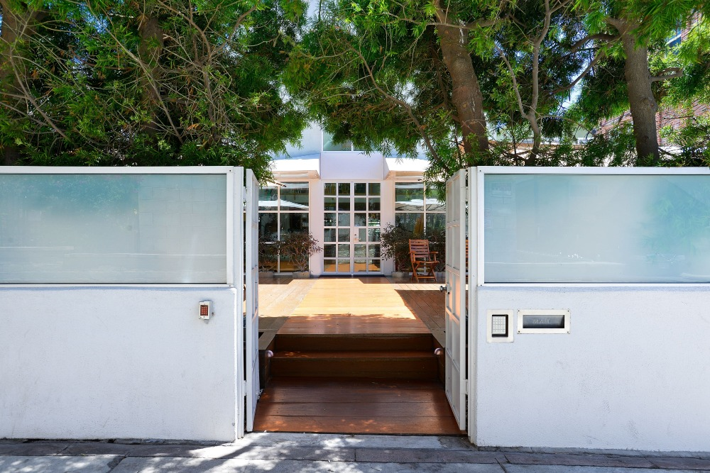 Closer look at this entry featuring a white gate and a white fence. Image courtesy of Toptenrealestatedeals.com.