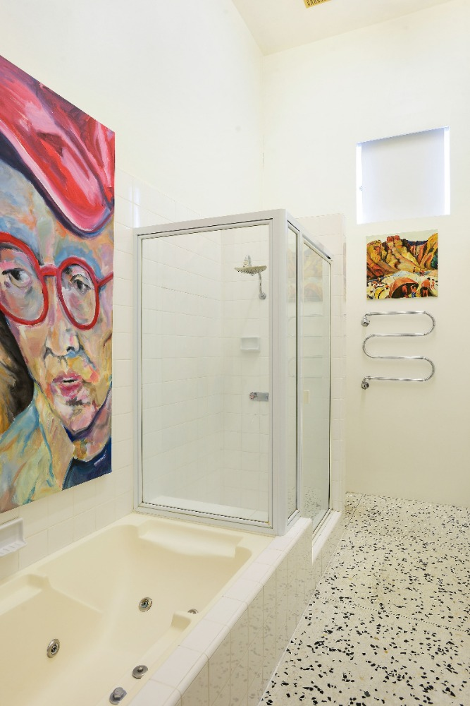 This bathroom features an artistic wall art on the side of the bathtub. Image courtesy of Toptenrealestatedeals.com.