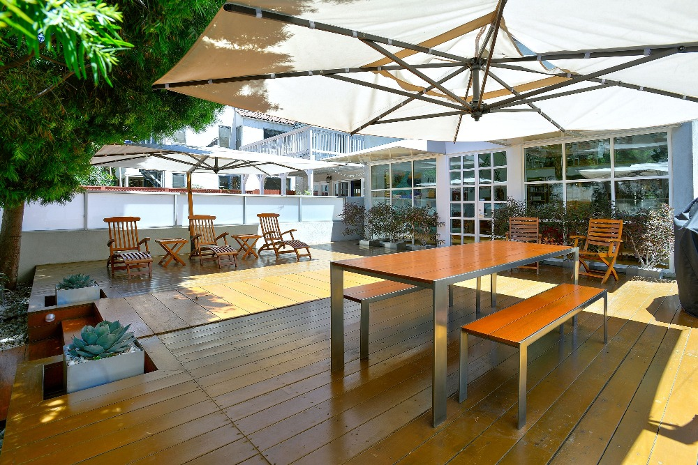 An outdoor deck featuring sitting lounges and an outdoor dining table set. Image courtesy of Toptenrealestatedeals.com.