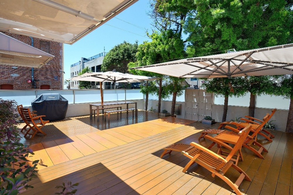 Another view at the home's deck showcasing its outdoor dining table and sitting lounges. Image courtesy of Toptenrealestatedeals.com.