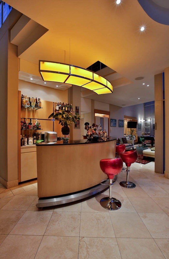 This is the bar with a curved island topped with a curved light. This area has consistent wooden elements on its bar, cabinetry and ceiling to make the stools stand out. Image courtesy of Toptenrealestatedeals.com.