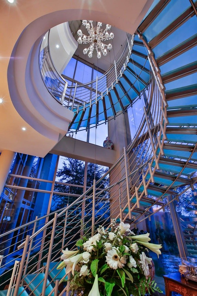 This is a view above the foyer. This shows the spiral stairal staircase with its metal railings and glass steps complemented by the glass wall. Image courtesy of Toptenrealestatedeals.com.