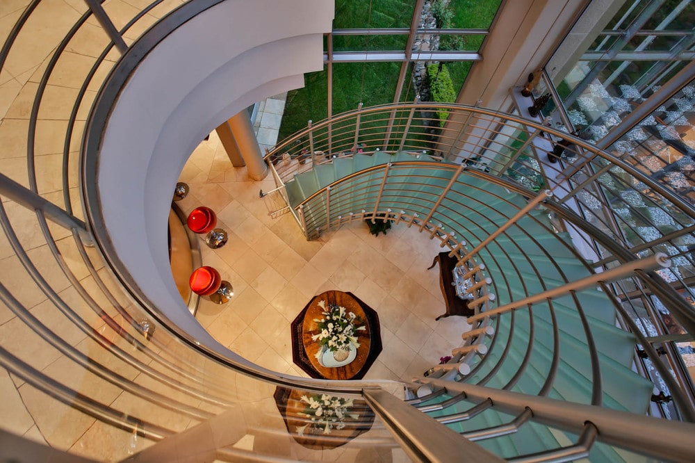 This is a look at the foyer below from the vantage of the second floor landing. This also gives a clear view of the spiral staircase with frosted glass steps. Image courtesy of Toptenrealestatedeals.com.