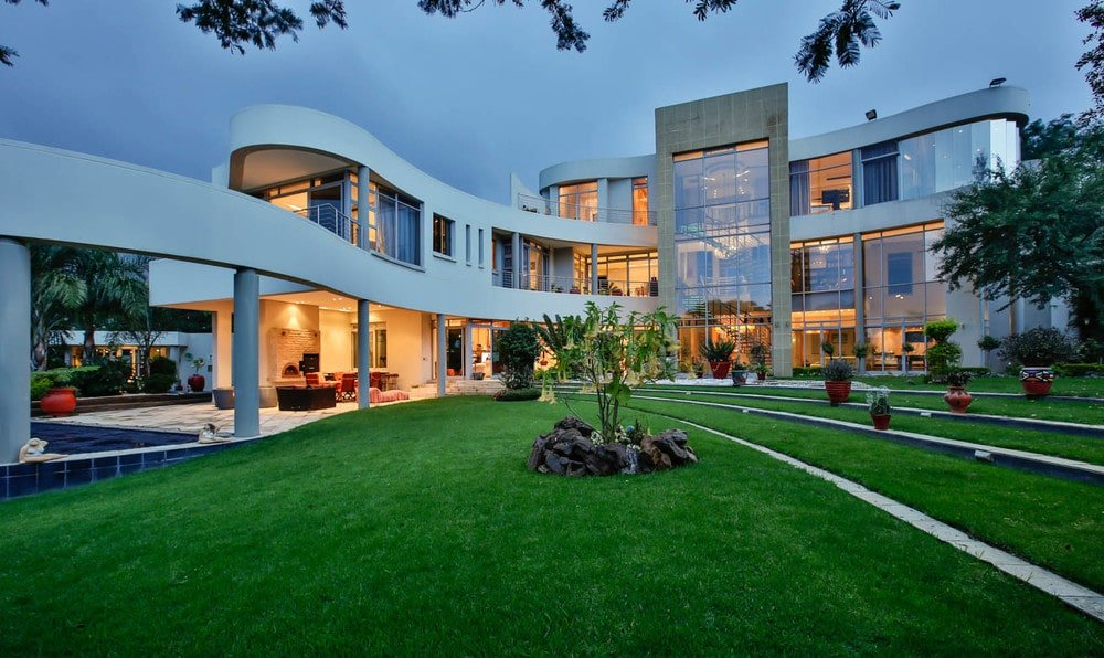 This is a front view of the contemporary-style home with a curved design complemented by glass walls and foregrounded by the landscaping. Image courtesy of Toptenrealestatedeals.com.