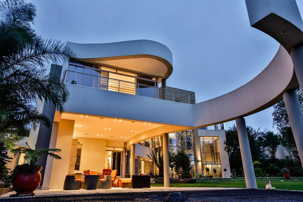 This is a close look at the covered patio beside the pool. You can also here the balcony above and the curved structure above the pool. Image courtesy of Toptenrealestatedeals.com.