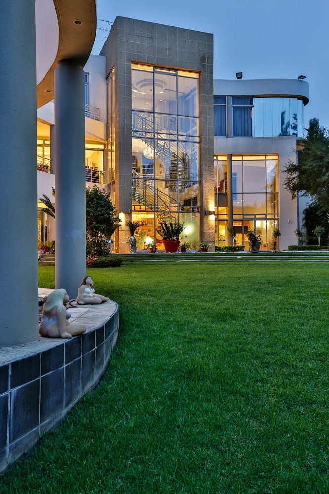 This view of the house showcases the large glass wall of the spiral staircase. This area is well-lit with warm yellow light. Image courtesy of Toptenrealestatedeals.com.
