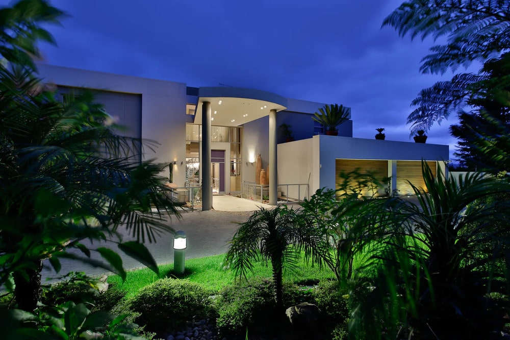 This is a look at the side of the house from the vantage of the surrounding landscape that is filled with trees, grass and complemented by the outdoor lights. Image courtesy of Toptenrealestatedeals.com.