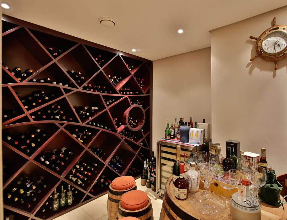 This is the wine cellar of the house with a maroon wooden structure dominating the wall with shelves for wine storage. The room also has a tasting area. Image courtesy of Toptenrealestatedeals.com.