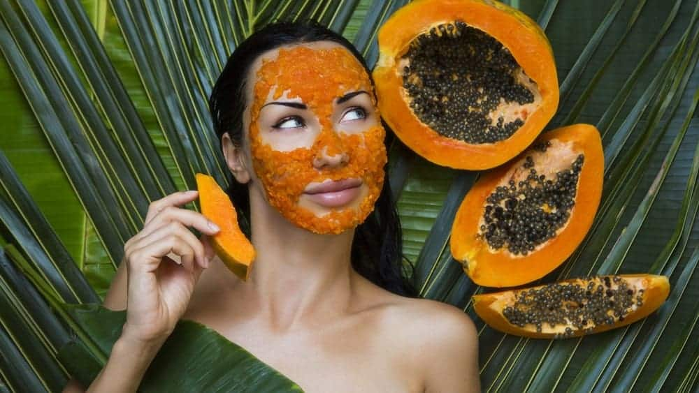 Woman applying a natural facial treatment using papaya.