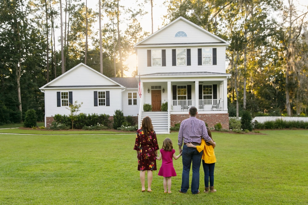 Back view of a family of four looking at their farmhouse home on a sprawling green lawn with trees behind the house.