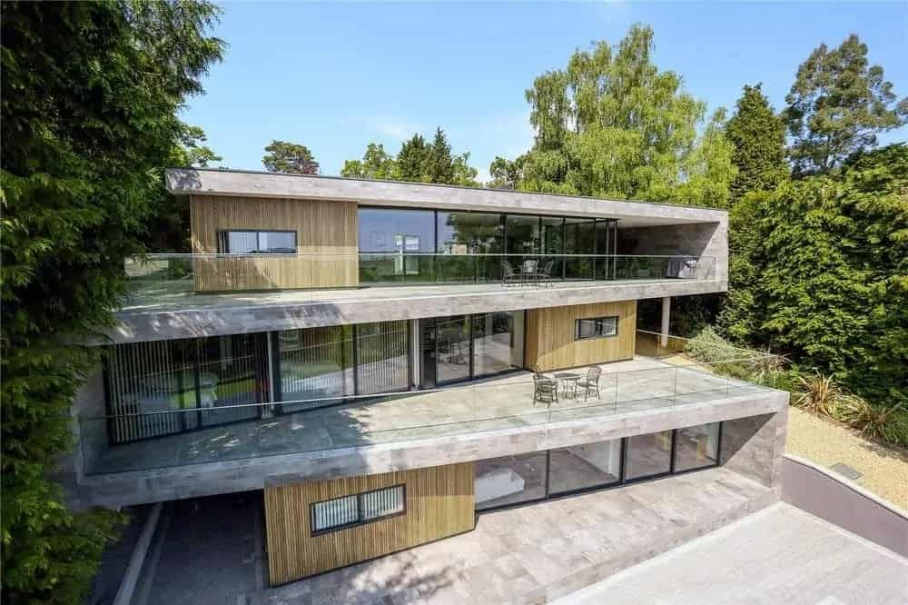 This is an aerial view of the house that showcases three levels of concrete, glass walls and sliding doors complemented by a few wooden walls that match well with the surrounding tall trees.