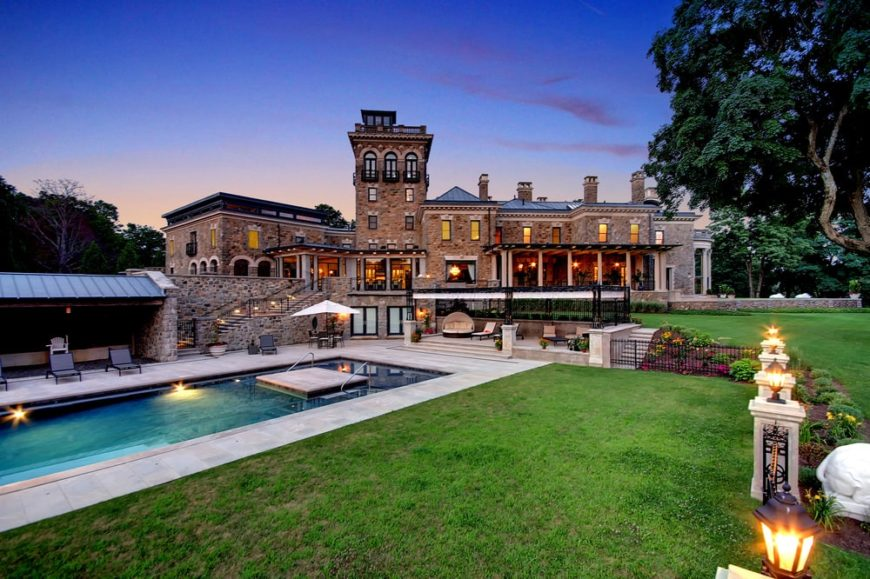 This is a view of the back of the house from the vantage of the poolside area. Here you can see the large estate and its earthy exterior walls complemented by the warm glow of the interiors. This also shows the tall towering chimneys on the roof. Image courtesy of Toptenrealestatedeals.com.