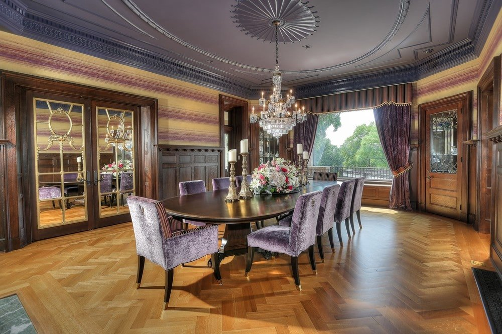 The formal dining room has a crystal chandelier hanging over the large dark wooden dining table that stands out against the herringbone pattern of the hardwood flooring. Image courtesy of Toptenrealestatedeals.com.
