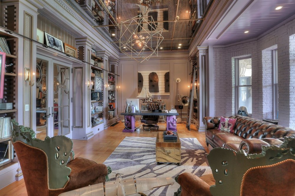 This is the spacious and airy living room. It has a soaring ceiling and tall walls, decorative lighting and a large patterned area rug in the middle of the hardwood flooring. Image courtesy of Toptenrealestatedeals.com.