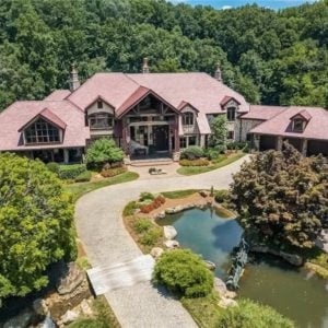 This is an aerial view of the front of the house that has earthy terracotta hues on its roof with various dormer windows and large glass walls complemented by the surrounding landscape of tall trees and shrubs. Image courtesy of Toptenrealestatedeals.com.