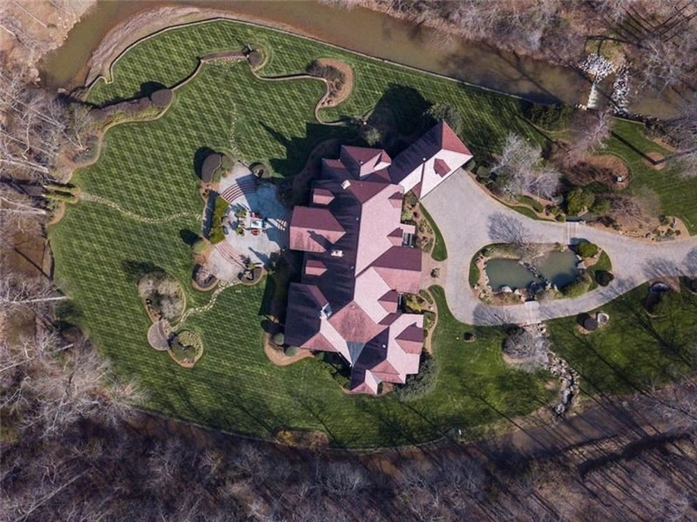 This is a top view of the large house showcasing the terracotta tone of the roof with various dormer windows that stand out against the surrounding green landscape. Image courtesy of Toptenrealestatedeals.com.