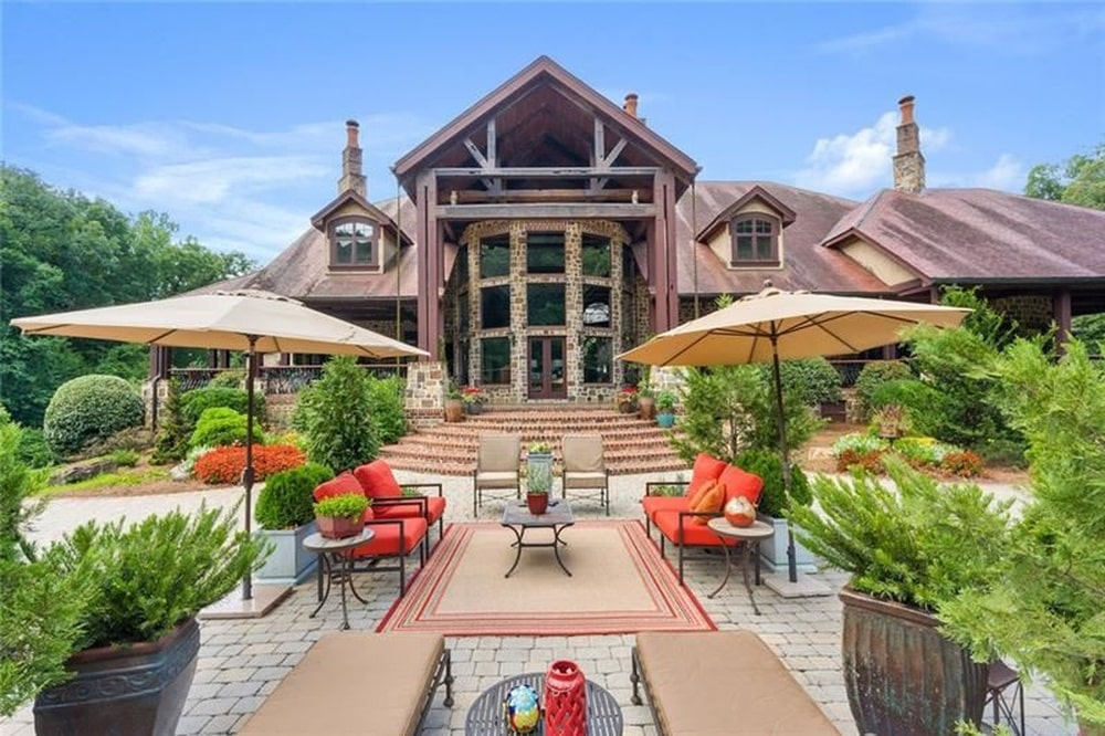 This is the back of the house just outside the large glass wall of the living room. This area is fitted with various sitting areas under large umbrellas adorned with shrubs. Image courtesy of Toptenrealestatedeals.com.