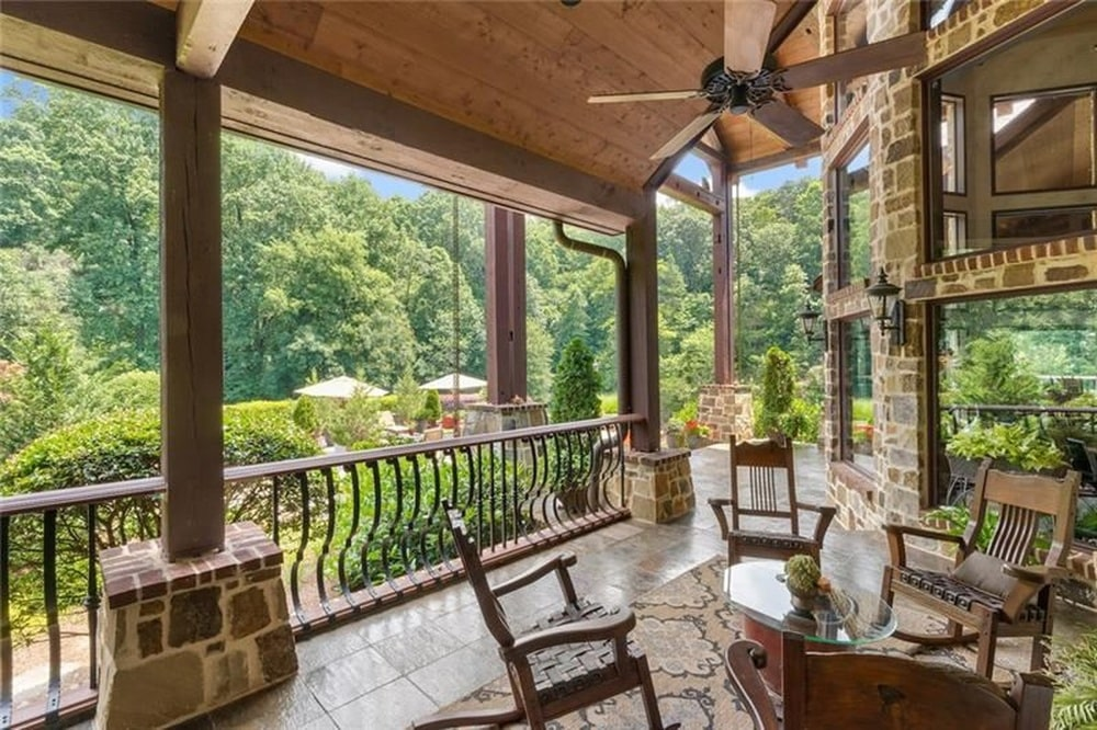 This is the balcony of the second level with an outdoor living room area facing a large stone structure that houses the fireplace and TV. You can also see here the railings and pillars of the balcony. Image courtesy of Toptenrealestatedeals.com.