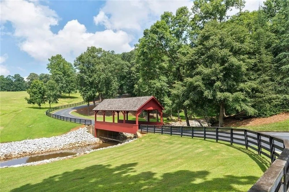 This is a close look at the wooden covered bridge of the driveway leading to the house. Image courtesy of Toptenrealestatedeals.com.