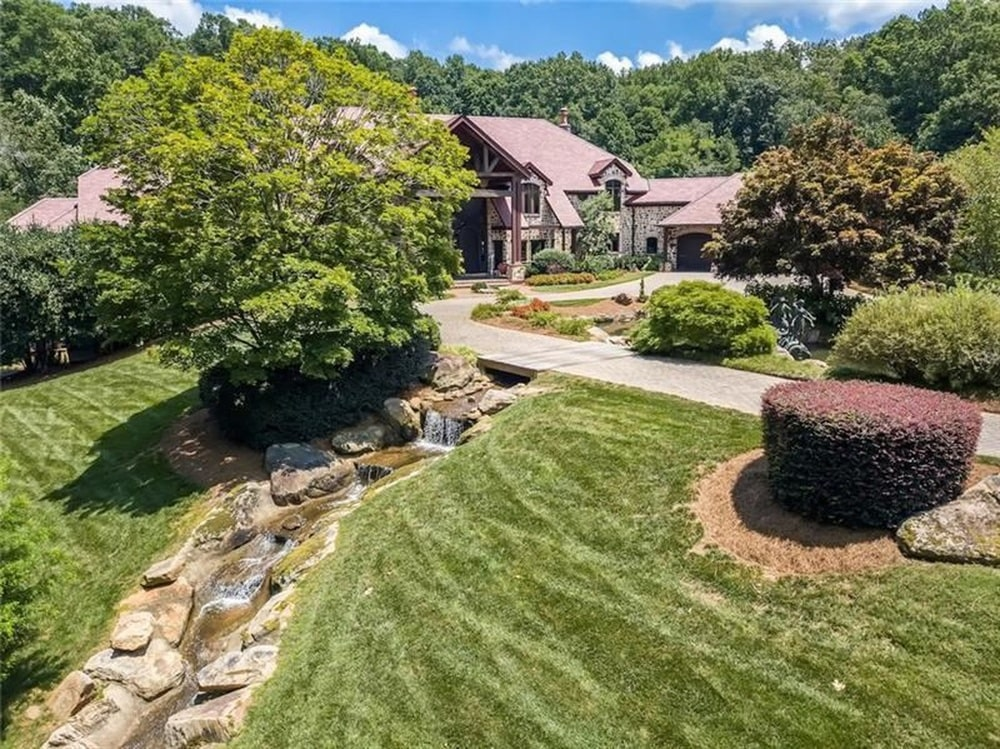 This angle of the front of the house shows the stream with decorative rocks and tall trees. Image courtesy of Toptenrealestatedeals.com.