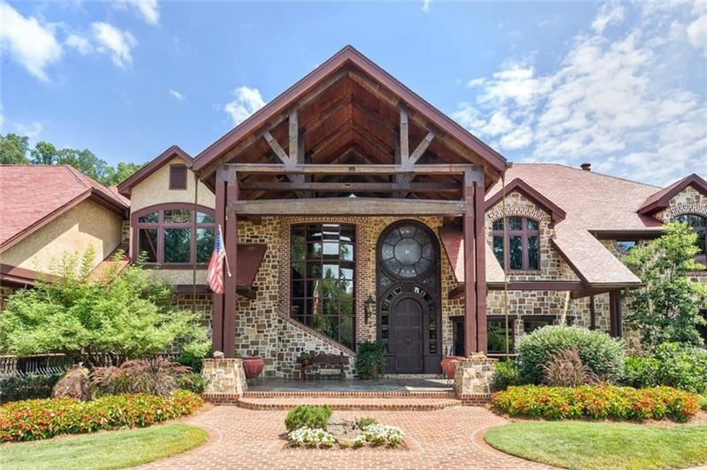 This is a closer look at the main entrance of the house with a tall wooden ceiling that has exposed beams and a large dark wooden main door. Image courtesy of Toptenrealestatedeals.com.