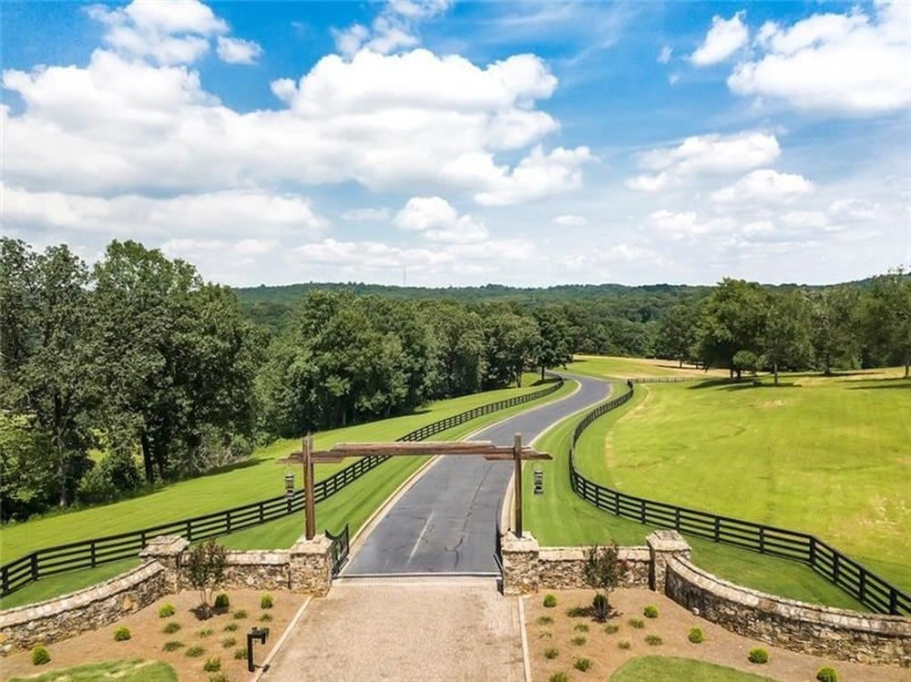 This is the main gate entrance of the property with a wooden arch and a wide driveway. Image courtesy of Toptenrealestatedeals.com.