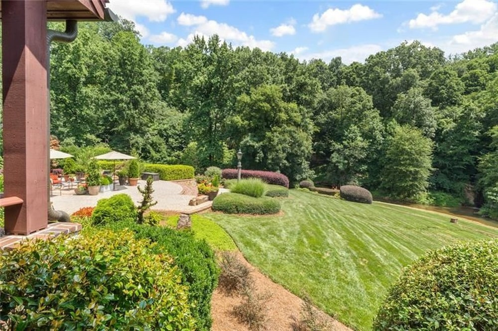 This is a look at the landscaping of the house with spacious grass lawns, shrubs and a background of tall trees. Image courtesy of Toptenrealestatedeals.com.