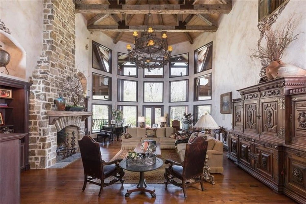 The large two-story living room has a stone fireplace and a large chandelier hanging from the tall wooden arched ceiling with beams. These are then complemented by the large glass wall at the far side. Image courtesy of Toptenrealestatedeals.com.