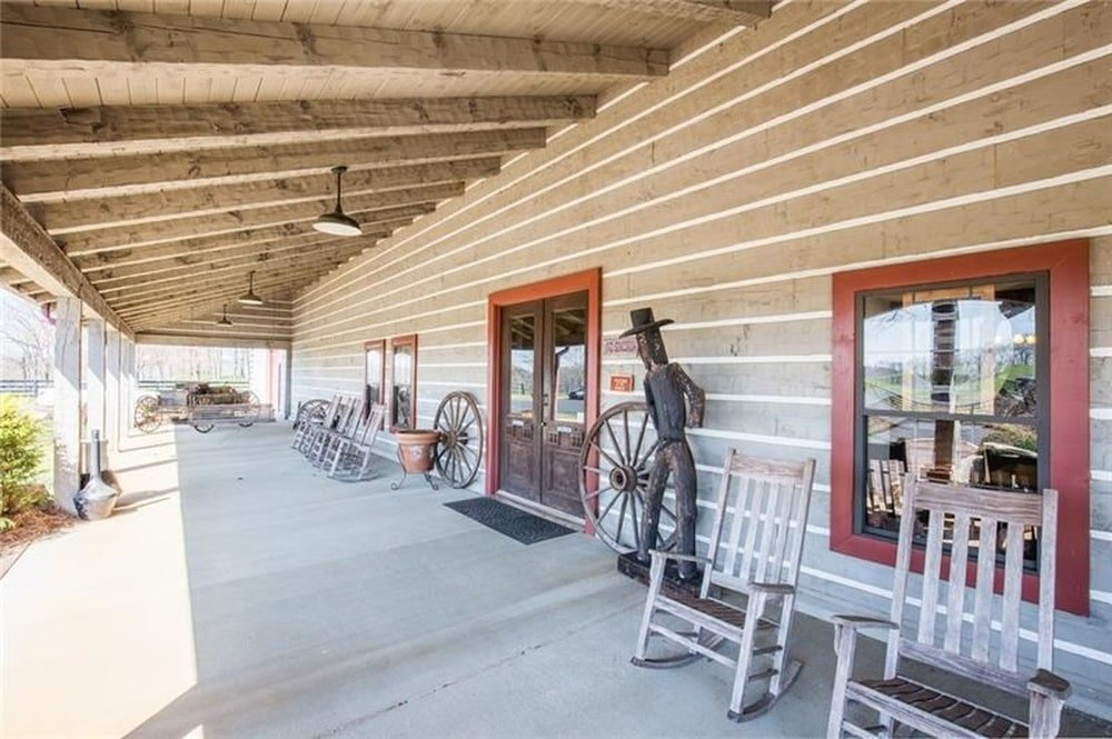This is a look at the wide porch of the house with various sitting areas and decors under a shed wooden ceiling. Image courtesy of Toptenrealestatedeals.com.