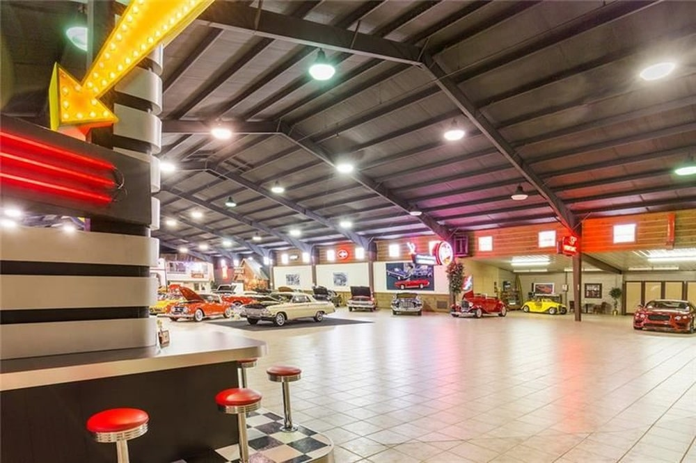 On the side of the showroom is a diner-style bar with fixed red stools and neon signs. Image courtesy of Toptenrealestatedeals.com.