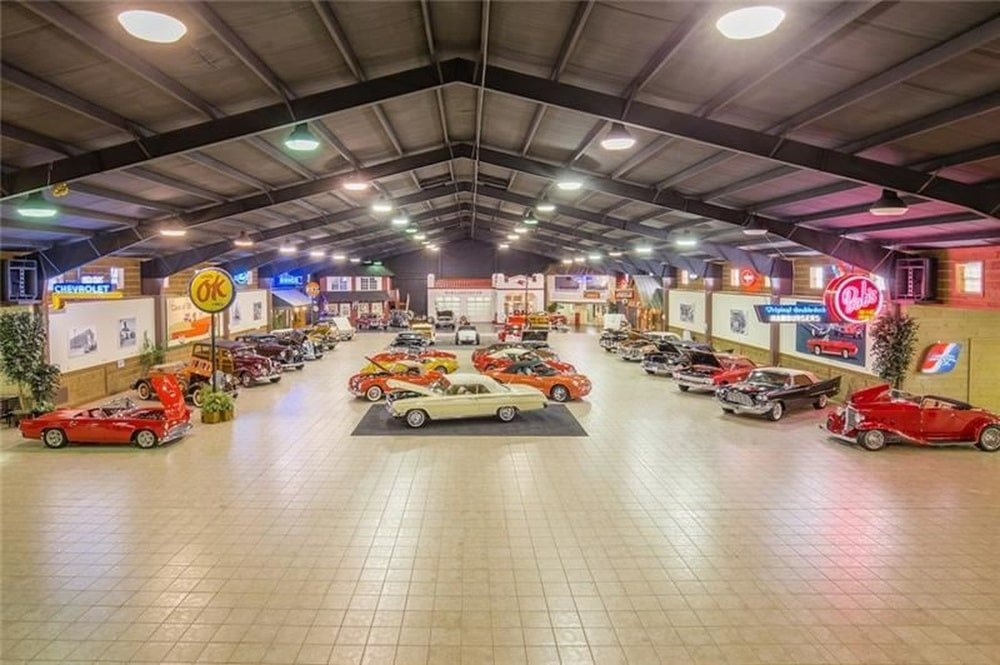 This is a look at the large showroom that can fit up to 70 cars on the spacious beige-tiled flooring. Image courtesy of Toptenrealestatedeals.com.