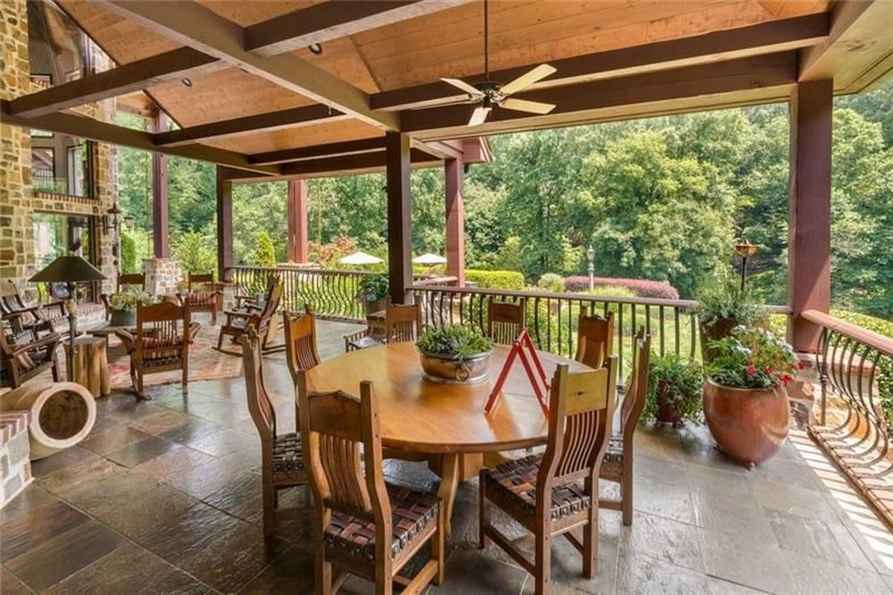 This is a look at the large terrace with a wooden beamed ceiling above an outdoor dining set with a wooden table and chairs adorned by potted plants. Image courtesy of Toptenrealestatedeals.com.
