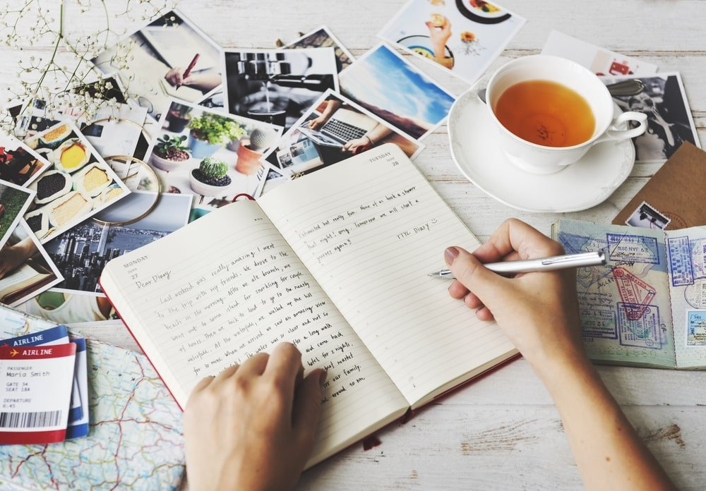 A person writing on a journal while drinking tea.