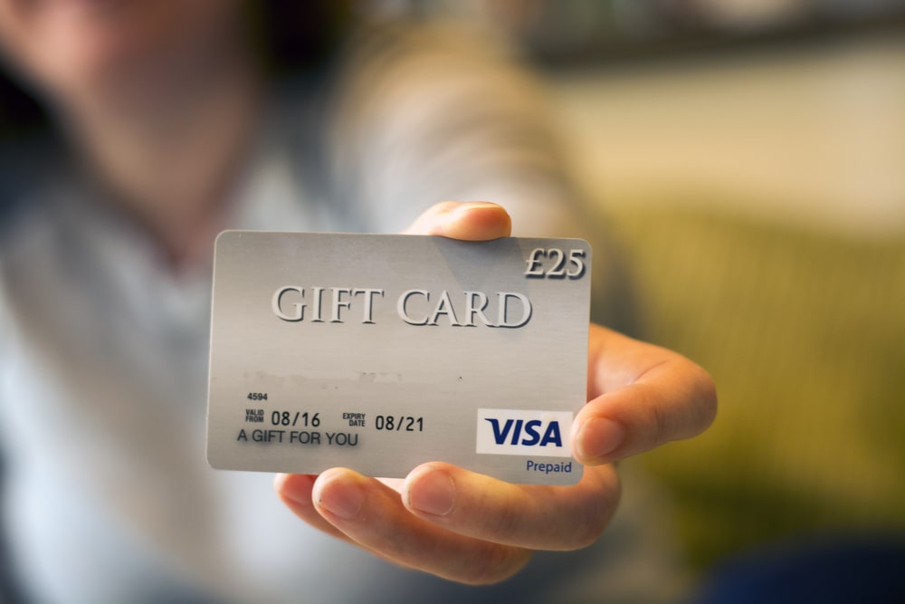A woman holding up a gift card.