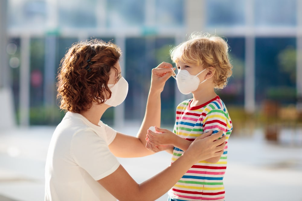A mother putting face mask on her kid.