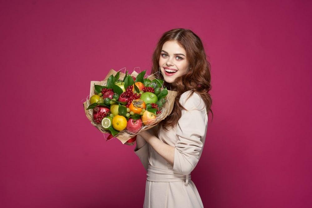 A woman holding a fruit bouquet.