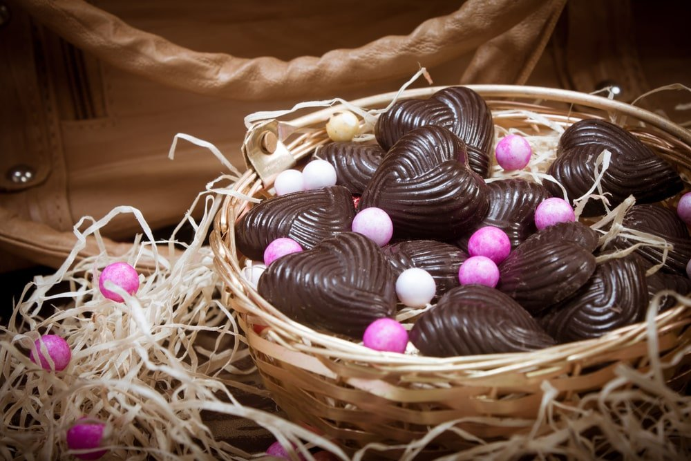A bunch of chocolate hearts in a basket.