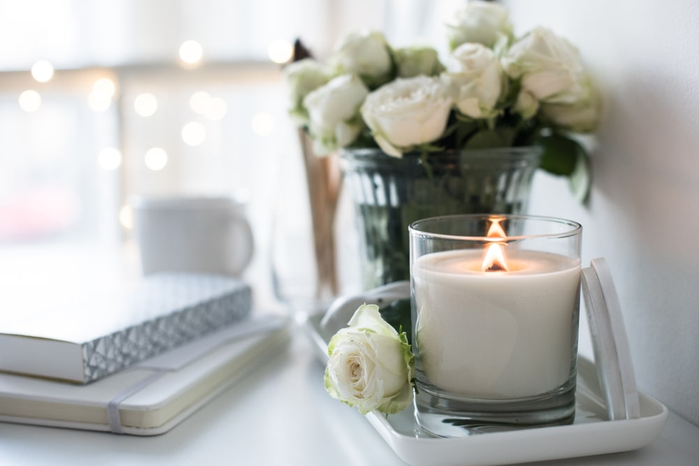 A white scented candle next to white roses.